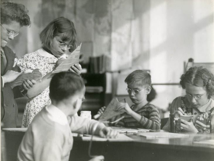 Black and white photograph of male and female students working on wood cutouts. Image taken circa 1938. Image from Ithaca's Open Air School Sight Saving Class. School began in 1917 to focus on students who were at high risk for tuberculosis. Sight Saving Class was begun to focus on students with visual impairments.